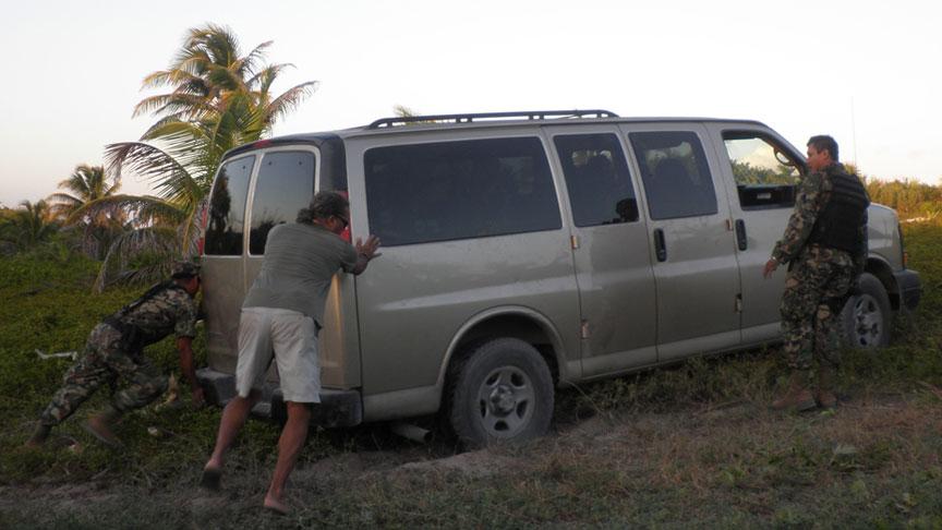 militares empujan una van atascada en la arena